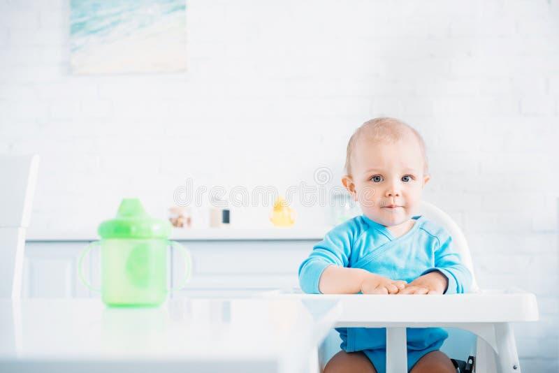 bebê pequeno bonito que senta-se na cadeira alta na cozinha e na vista fotos de stock