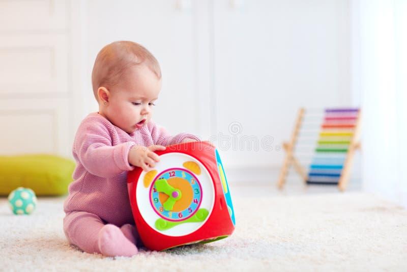 Bebê pequeno bonito que senta-se no tapete entre os brinquedos coloridos fotografia de stock