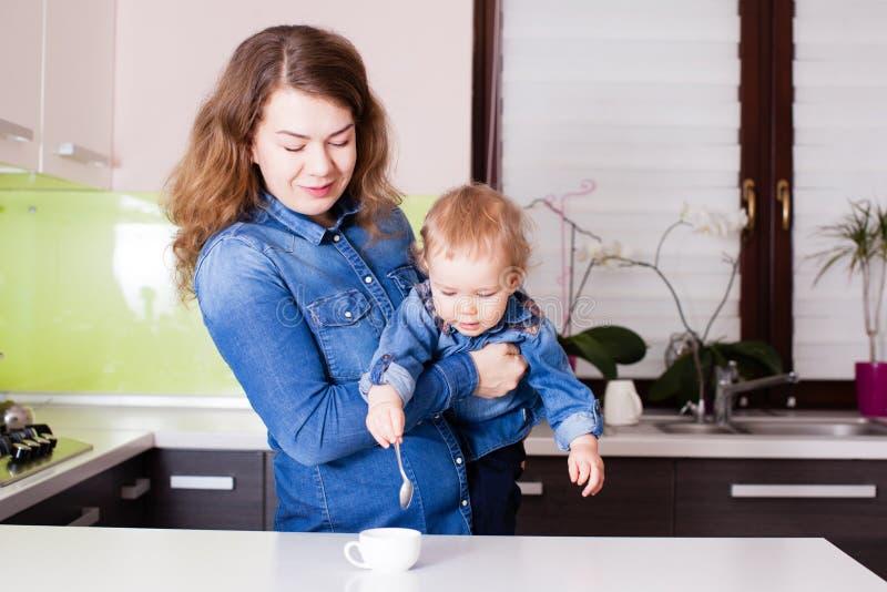 Bebê pequeno bonito que tenta ao café do stirr nos braços de sua mãe foto de stock royalty free