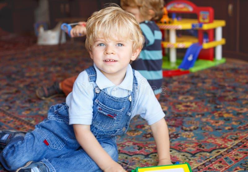 Bebê pequeno com os olhos azuis e os cabelos louros internos com caldo imagem de stock