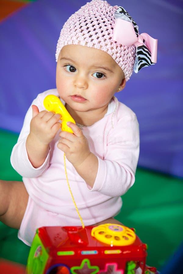 Bebê pequeno com um telefone do brinquedo foto de stock royalty free