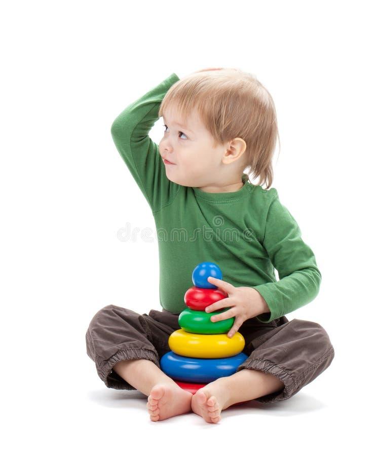 Bebê pequeno com uma pirâmide do brinquedo imagem de stock