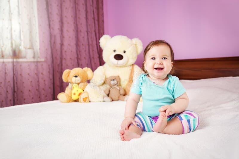 Bebê pequeno de sorriso bonito que senta-se na cama com brinquedos macios fotos de stock