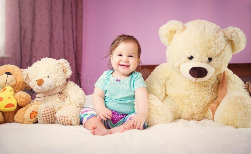 Bebê pequeno de sorriso bonito que senta-se na cama com brinquedos macios imagem de stock