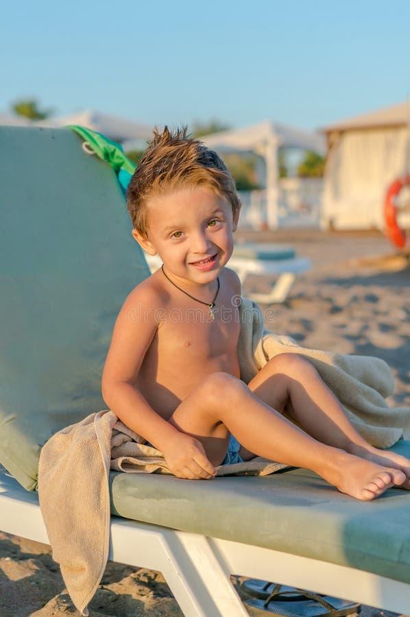 Bebê pequeno de sorriso do retrato que senta-se perto do mar, oceano Emoções humanas positivas, sentimentos, alegria Criança boni imagem de stock