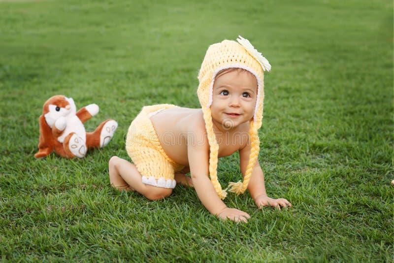 Bebê pequeno de sorriso feliz bonito que rasteja no parque imagens de stock