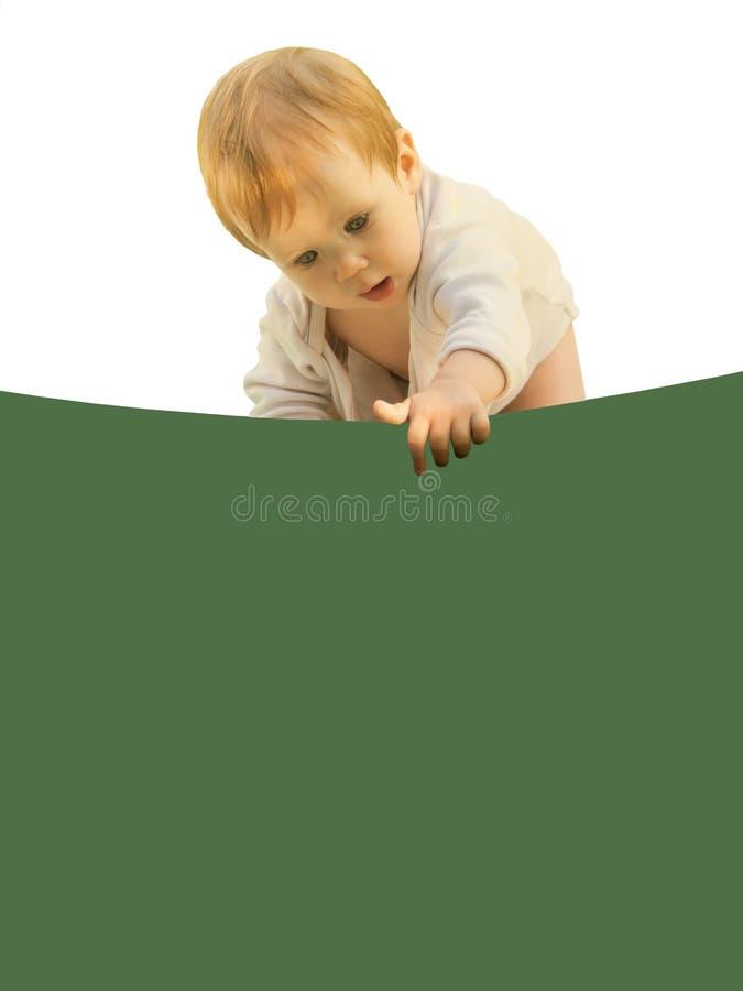 Bebê pequeno do bebê dobrado curiosamente sobre a folha colorida imagens de stock