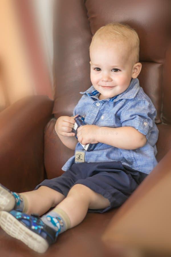 Bebê pequeno do retrato que senta-se na cadeira de couro marrom e que sorri dentro 1,5 anos de criança idosa que joga na sala imagem de stock royalty free