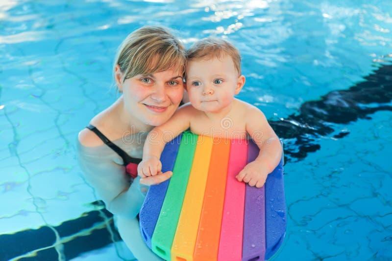 Bebê pequeno e sua mãe que aprendem nadar em um swi interno imagens de stock royalty free