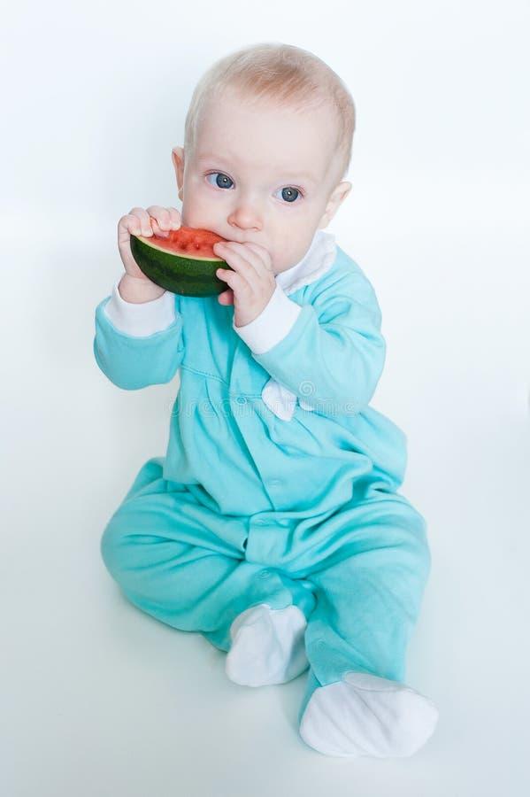 Bebê pequeno engraçado bonito no macaquinho de turquesa com a melancia isolada no fundo branco imagem de stock