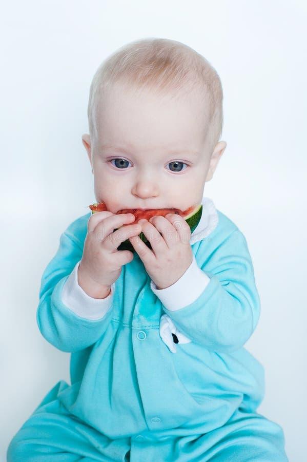 Bebê pequeno engraçado bonito no macaquinho de turquesa com a melancia isolada no fundo branco fotografia de stock