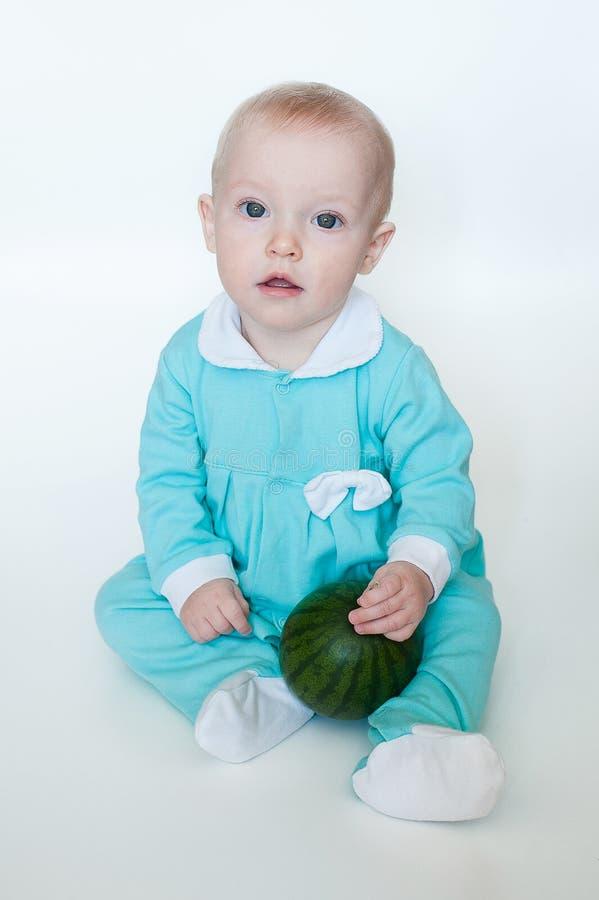 Bebê pequeno engraçado bonito no macaquinho de turquesa com a melancia isolada no fundo branco imagens de stock royalty free