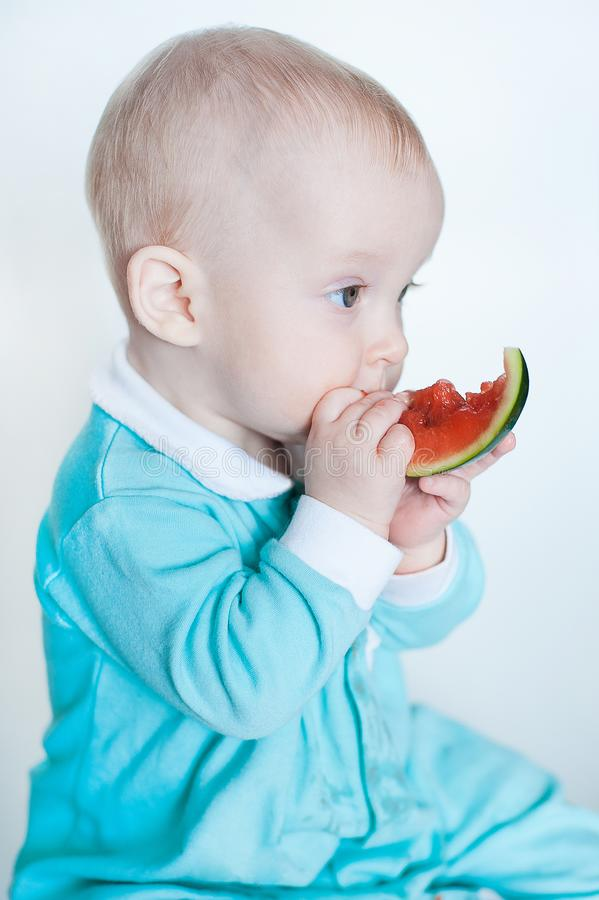 Bebê pequeno engraçado bonito no macaquinho de turquesa com a melancia isolada no fundo branco foto de stock royalty free
