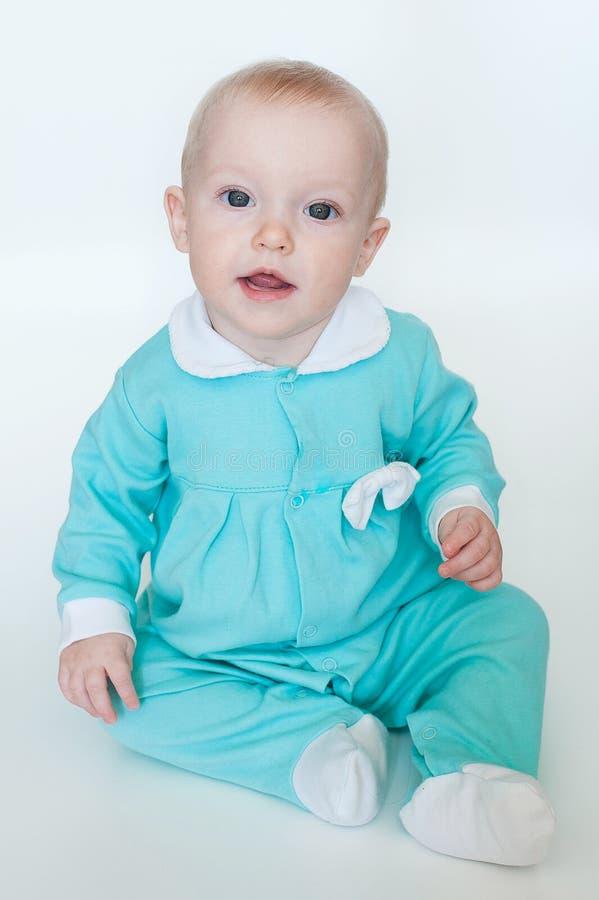 Bebê pequeno engraçado bonito no macaquinho de turquesa isolado no fundo branco imagens de stock royalty free