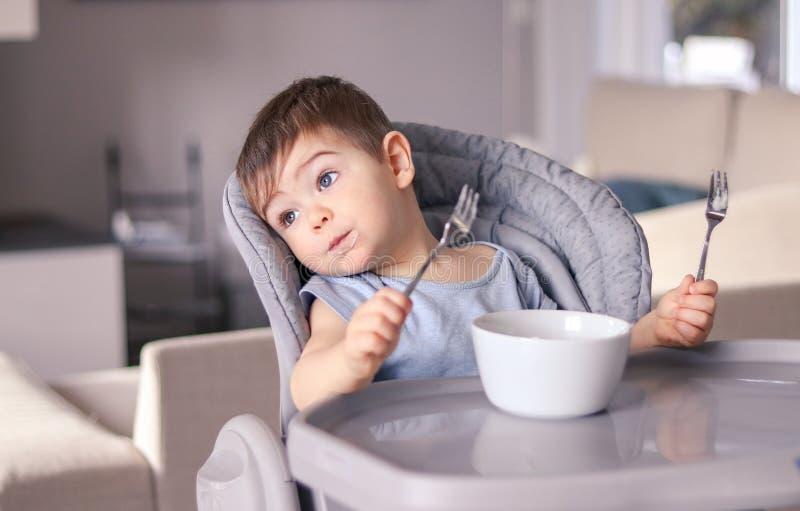 Bebê pequeno engraçado pensativo adorável com cara manchada e duas forquilhas nas mãos cansados da inclinação comer na cadeira de imagem de stock royalty free