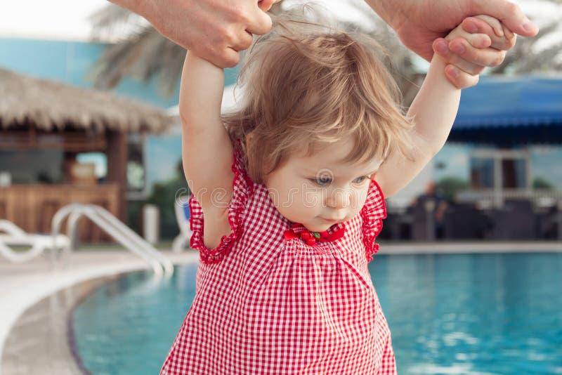 Bebê pequeno engraçado perto da piscina O pai guarda o infante pelas mãos no fundo da associação Férias de verão com foto de stock royalty free