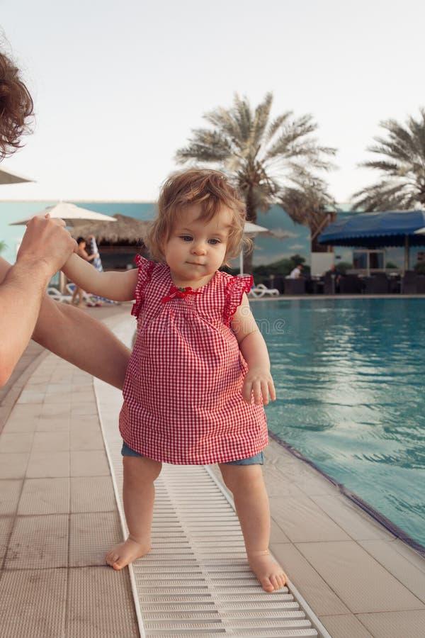 Bebê pequeno engraçado perto da piscina O pai guarda o infante pelas mãos no fundo da associação Férias de verão com fotografia de stock royalty free