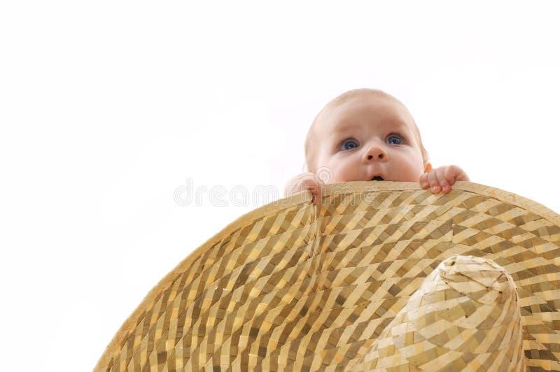 Bebê pequeno escondido atrás de um chapéu grande, retrato imagem de stock