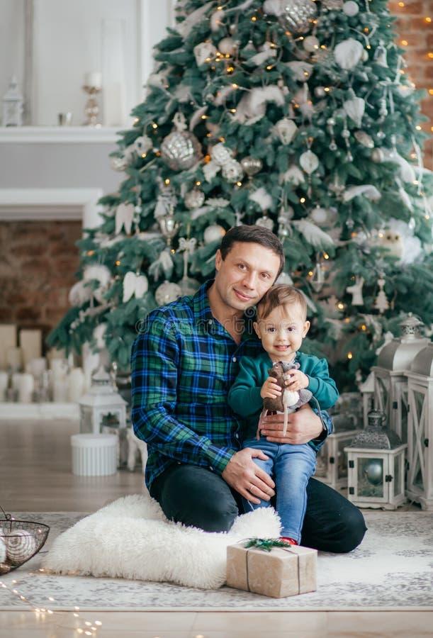 Beb? pequeno feliz com o pai perto da ?rvore de Natal com presentes foto de stock