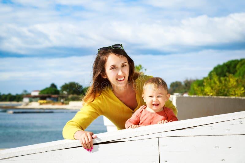 Bebê pequeno feliz e mãe de sorriso pelo mar imagem de stock