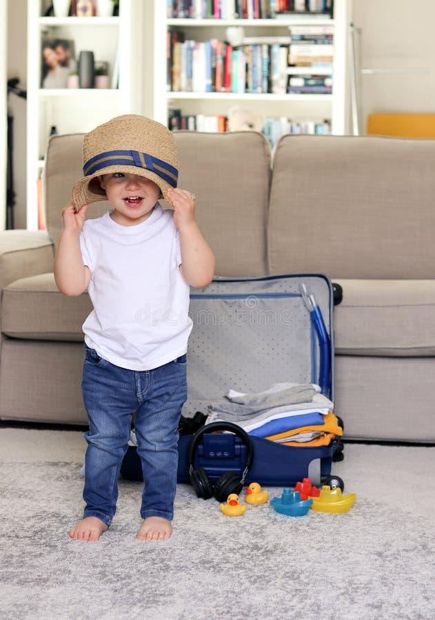 Bebê pequeno feliz engraçado bonito que fica em casa pondo o chapéu de palha sobre a cabeça com a mala de viagem azul no fundo em fotografia de stock royalty free