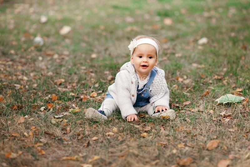 Bebê pequeno feliz que senta-se na grama no parque, jardim, prado O bebê olha pais, tempo morno bonito fotos de stock royalty free