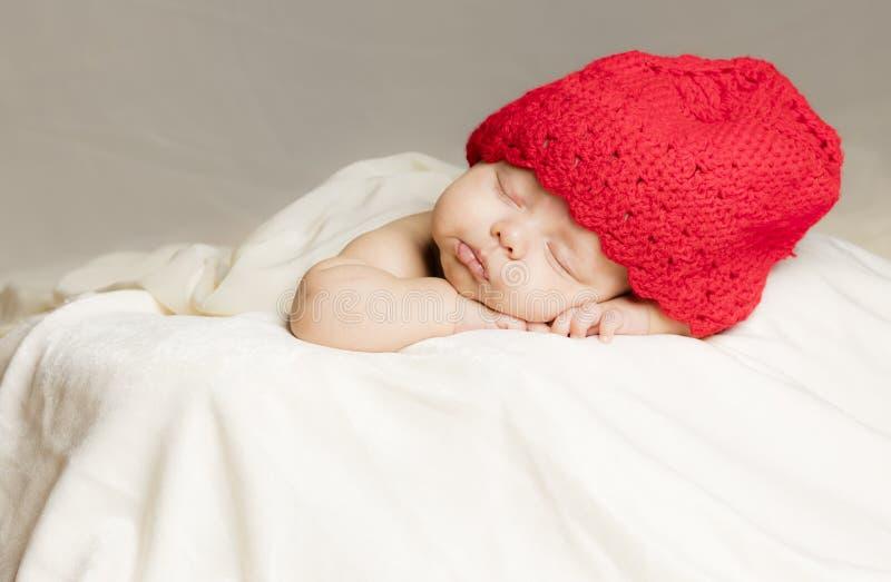 Bebê pequeno na cama com chapéu vermelho fotografia de stock