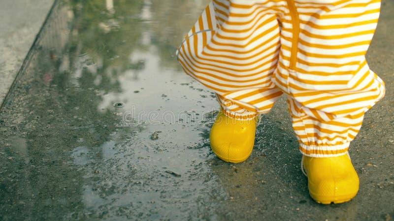 Bebê pequeno na capa de chuva impermeável listrada alaranjada e em caminhadas de borracha amarelas em poças após a chuva, close-u fotografia de stock