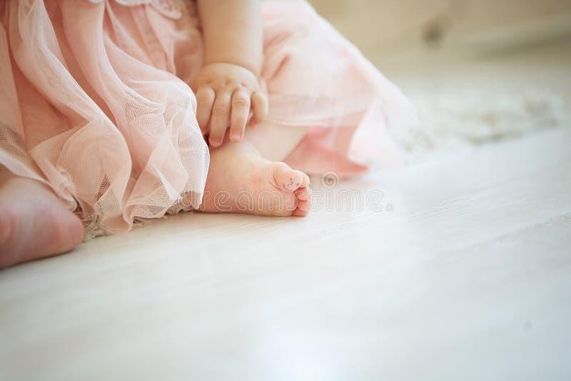 Bebê pequeno no assoalho com a cara tirada do smiley em seu dedo grande do pé fotos de stock