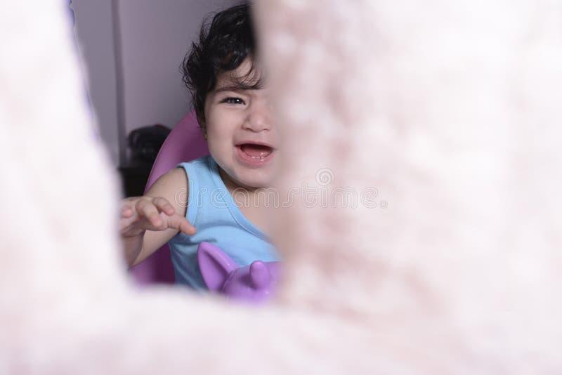 Bebê pequeno no balanço do unicórnio que grita para o urso de peluche imagem de stock