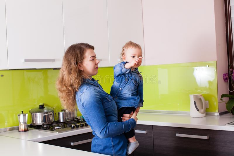 Bebê pequeno nos braços da mãe em sua cozinha fotografia de stock