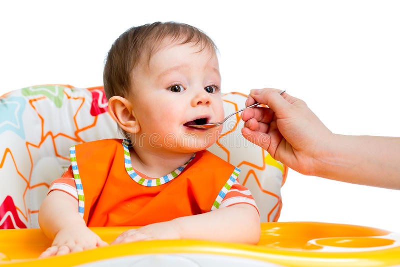 Bebê pequeno que alimenta com uma colher imagens de stock