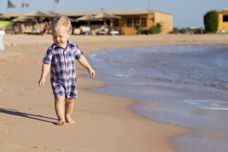 Bebê pequeno que anda o beira-mar oncept para o anúncio do curso Copie o espaço foto de stock