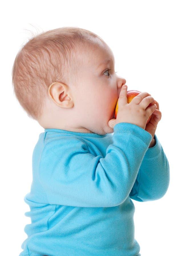 Bebê pequeno que come a maçã vermelha fotografia de stock royalty free