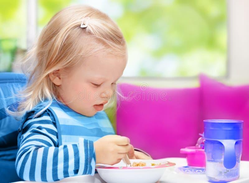 Bebê pequeno que come o café da manhã foto de stock royalty free