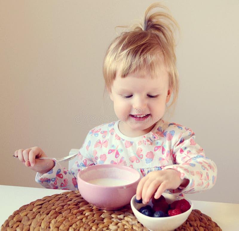 Bebê pequeno que come o café da manhã saudável em casa, as bagas e o iogurte fotos de stock