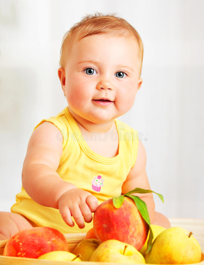 Bebê pequeno que escolhe frutas fotos de stock