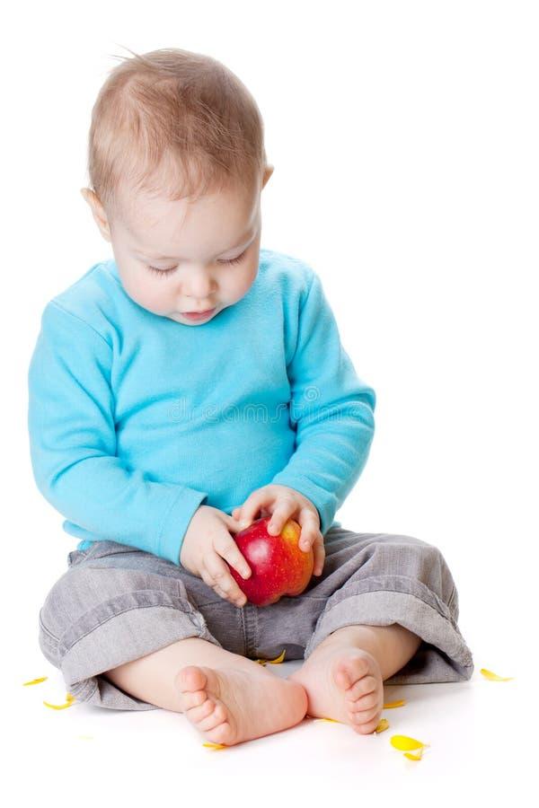 Bebê pequeno que prende a maçã vermelha foto de stock royalty free