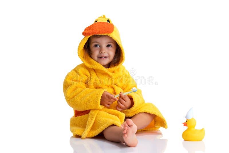 Bebê pequeno que sorri sob uma toalha amarela e que escova seus dentes fotos de stock royalty free