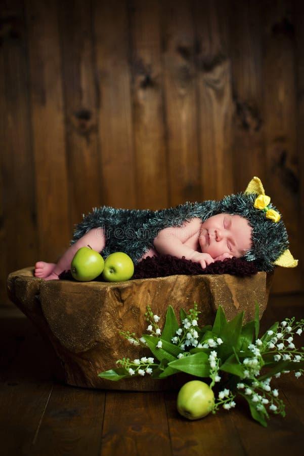 Bebê pequeno recém-nascido engraçado em um traje do ouriço que dorme docemente no coto fotografia de stock royalty free