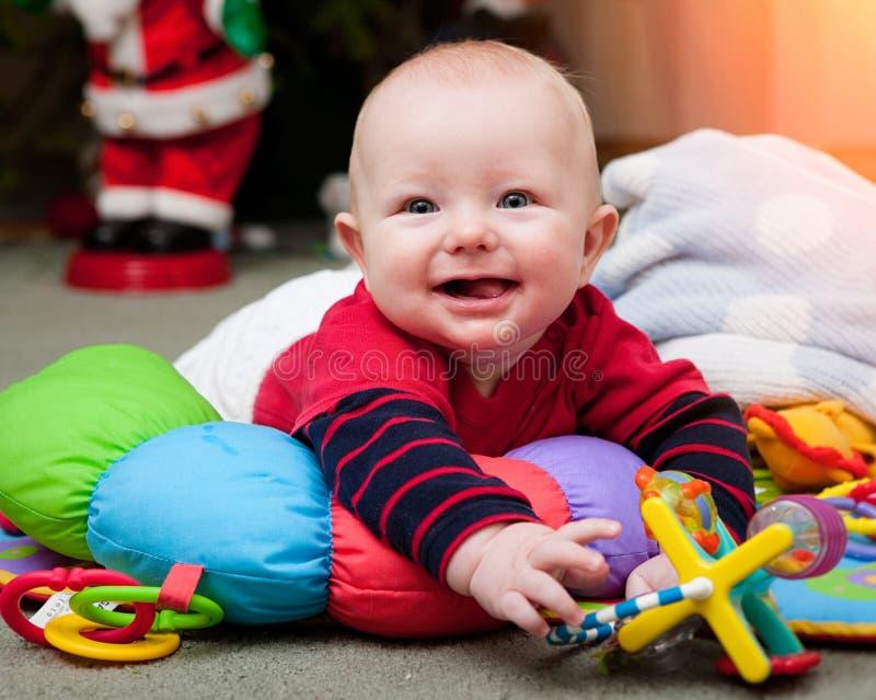 Bebê pequeno sob a árvore de Natal, sorrindo e jogando fotografia de stock royalty free