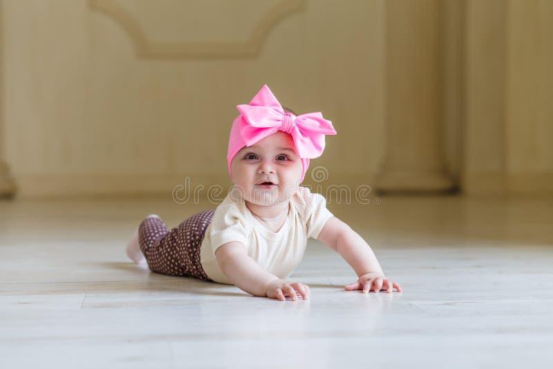 Bebê pequeno surpreendido no assoalho no interior da casa ou do estúdio 6 meses bonitos bonitos da menina com uma curva cor-de-ro imagens de stock