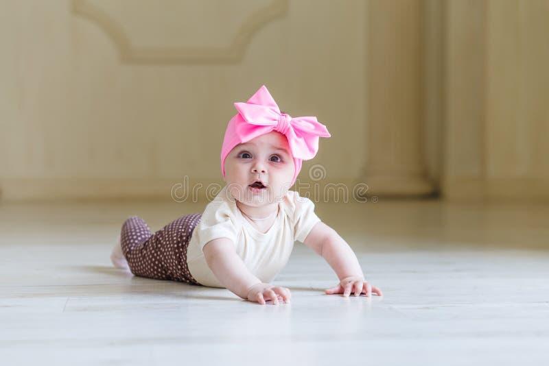 Bebê pequeno surpreendido no assoalho no interior da casa ou do estúdio 6 meses bonitos bonitos da menina com uma curva cor-de-ro fotos de stock royalty free