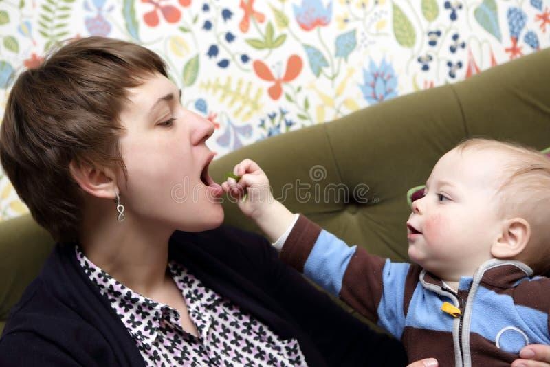 Bebê que alimenta sua mãe imagens de stock