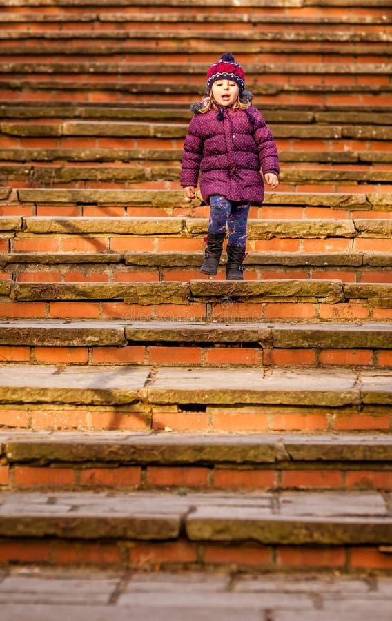 Bebê que anda abaixo das escadas velhas foto de stock