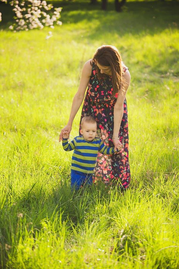 Bebê que anda no parque verde que guarda as mãos da mãe fotografia de stock