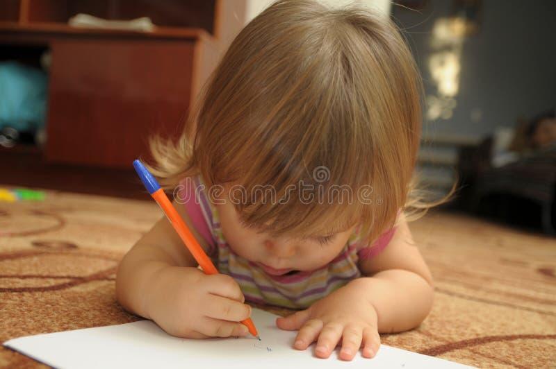 Bebê que aprende escrever e pintar no ambiente familiar que encontra-se no tapete Conceito adiantado do desenvolvimento da educaç fotografia de stock