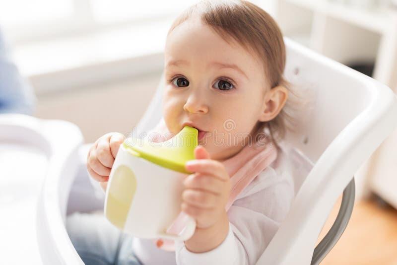 Bebê que bebe do copo do bico no cadeirão em casa foto de stock