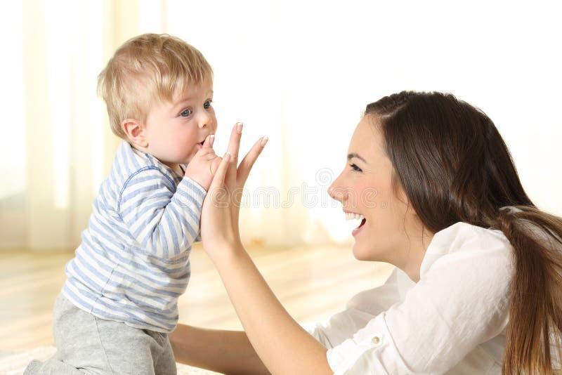 Bebê que beija seu dedo da mãe imagens de stock royalty free