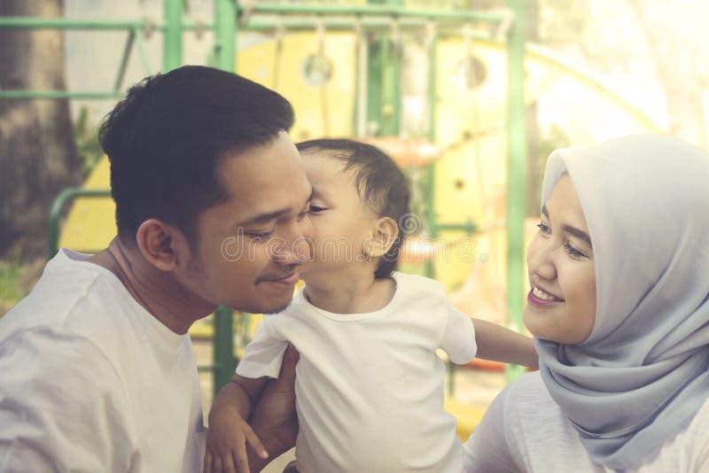 Bebê que beija seus pais no campo de jogos foto de stock royalty free